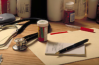 Still life: doctor's desk with pill bottle, prescription pad and stethoscope