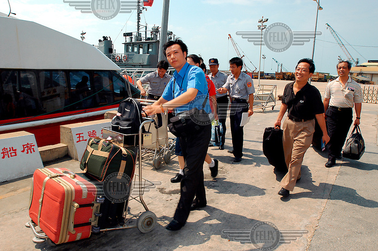 Passengers board the new ferry service direct to mainland China. Part of an experiment known as the '3 mini links', whereby residents of the Taiwanese islands closest to China are allowed to travel to Fujian province.