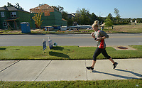 NWA Democrat-Gazette/ANDY SHUPE<br /> A runner makes her way along Salem Road Saturday, Sept. 9, 2017, past houses being constructed south of Wedington Drive in Fayetteville. Local builders are unable to keep pace with demand for houses in the area, and are branching out into smaller communities in Northwest Arkansas.