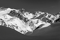 Spring landscape of man snowshoeing and viewing the snow-covered Talkeetna Mountains in the Mint Glacier Area of the Hatcher Pass Managmement Area of the Matanuska Valley  Spring Southcentral, Alaska   Model Released<br /> <br /> Photo by Jeff Schultz (C) 2016  ALL RIGHTS RESERVED