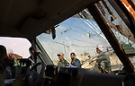 Rebels are seen through the broken windshield of a fighter's truck on the road near the city of Ajdabiya, Libya, March 24, 2011. Despite air strikes from Western war planes, which crippled Col. Muammar Qaddafi's military capability, the rebels seemed unable to advance and retake the city.