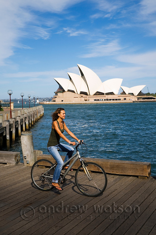 A woman cycles along a boardwalk on Sydney Cove with the Opera House beyond.  Sydney, New South Wales, AUSTRALIA.