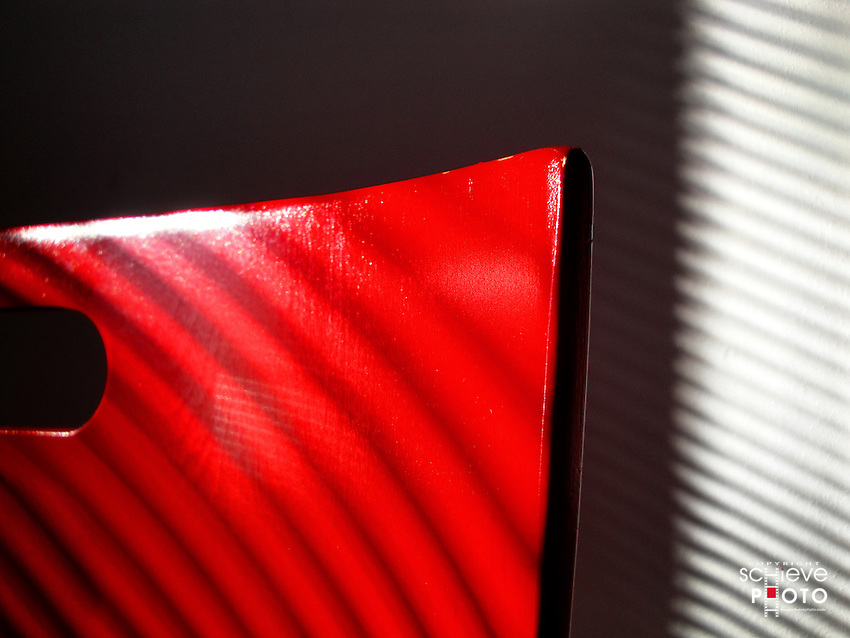 Sunlight filtering through blinds onto a red chair.