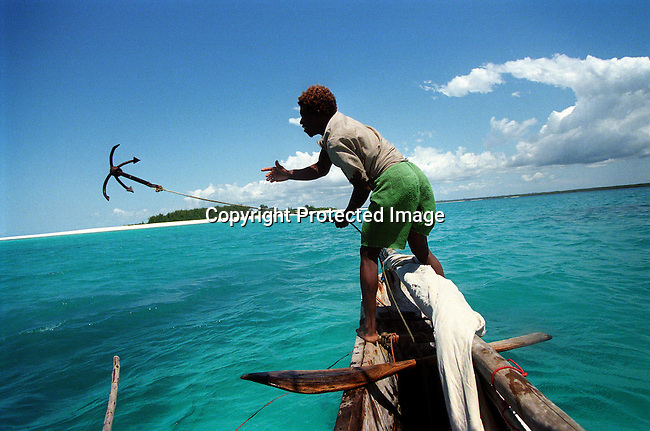 A fisherman throws his anchor as he is sailing a traditional boat along the coast on July 15, 1997, outside Matemwe, Zanzibar. The island has a long history with slave trade and was ruled by Omani Arabs during the early 19th century. The Island is predominately Muslim and has become a popular tourist destination in recent years. The Island is a two-hour boat ride from Dar Es Salaam, Tanzania on the east African coast. The island is part of Tanzania. (Photo by: Per-Anders Pettersson)