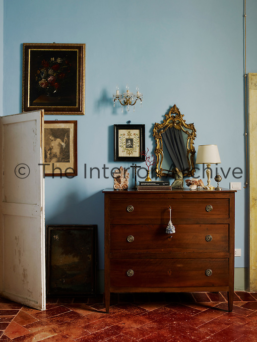 A simple chest of drawers on which is displayed a few personal items occupies one wall of the bedroom