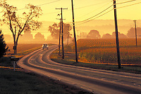 Car on country road at sunrise. Strasburg Pennsylvania USA Lancaster County.