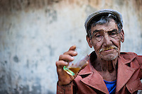 An old sugar-cane cutter (machetero) drinks rum in front of an apartment block in Bahía, a public housing periphery of Havana, Cuba, 11 February 2011.