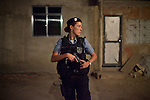 UPP officer Carla Bon, during patrol in Complexo do Caju, Rio de Janeiro, Brazil, on Friday May 10, 2013.<br /> <br /> In the early hours of Sunday, March 3, 2013, about 1,400 Brazilian security forces occupied 13 communities during a joint public security operation to install a Pacifying Police Unit (UPP) in two Rio de Janeiro favelas, Complexo do Caju and Barreira do Vasco. Elite police units backed by armored military vehicles and helicopters invaded the neighborhood in an on-going policing program aimed to drive violent and heavily armed drug gangs out of Rio's poor communities, where the traffickers have ruled for decades. For the community of Caju, that is ADA (Amigos de Amigos) and CV (Comando Vermelho).