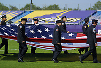 Members of the New York City Police and Fire Department's soccer teams carry a flag that flew at the World Trade Center into Mitchel Atletic Complex prior to the start of the May 25th game between the New York Power and the San Diego Spirit.