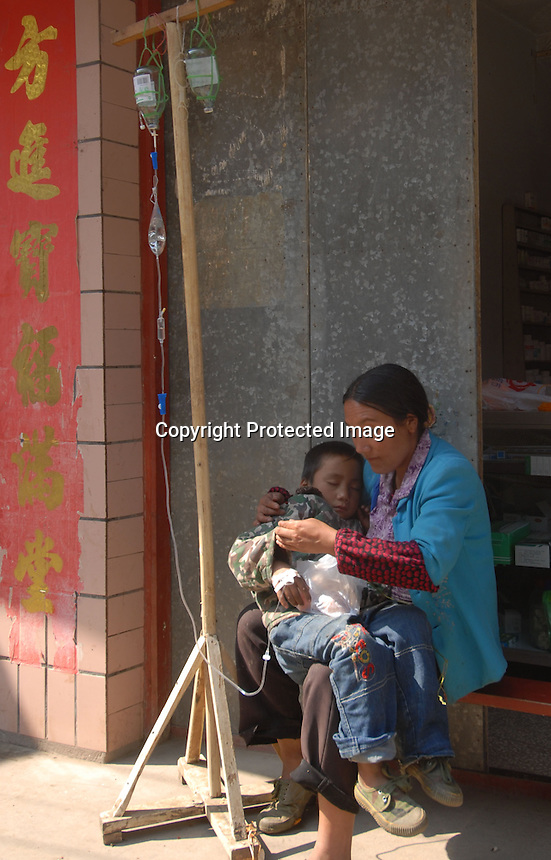 "A boy recieves medical care from a drip on the side of a street at Shabao village, the nearest large village to China's ""Space Launch Centre"" in Sichuan Province, China. The Chinese made Long March Rocket called Chang'e 1, was launched 24th October 2007, Sichuan Province, China."