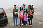 A middle class family pose next to their Chevrolet at the Buddhist Stupor. Dochula mountain pass connecting Thimpu, Punakha, Bumthang and Gangtey..Bhutan the country that prides itself on the development of 'Gross National Happiness' rather than GNP. This attitude pervades education, government, proclamations by royalty and politicians alike, and in the daily life of Bhutanese people. Strong adherence and respect for a royal family and Buddhism, mean the people generally follow what they are told and taught. There are of course contradictions between the modern and tradional world more often seen in urban rather than rural contexts. Phallic images of huge penises adorn the traditional homes, surrounded by animal spirits; Gross National Penis. Slow development, and fending off the modern world, television only introduced ten years ago, the lack of intrusive tourism, as tourists need to pay a daily minimum entry of $250, ecotourism for the rich, leaves a relatively unworldly populace, but with very high literacy, good health service and payments to peasants to not kill wild animals, or misuse forest, enables sustainable development and protects the country's natural heritage. Whilst various hydro-electric schemes, cash crops including apples, pull in import revenue, and Bhutan is helped with aid from the international community. Its population is only a meagre 700,000. Indian and Nepalese workers carry out the menial road and construction work.