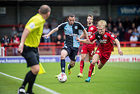 Michael Harriman of Wycombe Wanderers  and Christian Scales of Crawley Town  battle down the line under the watchful eye of the assistant referee during the Sky Bet League 2 match between Crawley Town and Wycombe Wanderers at Checkatrade.com Stadium, Crawley, England on 29 August 2015. Photo by Liam McAvoy.