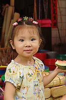 Chinese toddler eating watermelon, Fuli Village market, Yangshuo, China