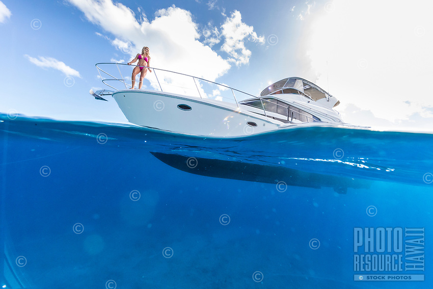 A woman enjoys the view from a power cruiser off of Waikiki, O'ahu.