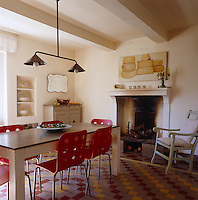 A classic French kitchen has been modernised with a bright tiled floor and a set of red retro chairs