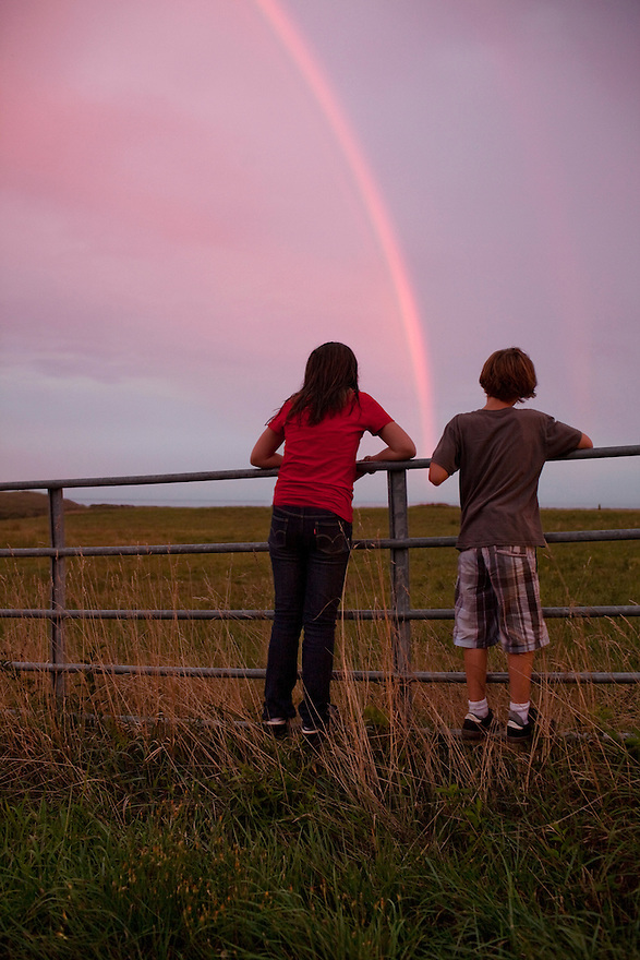 Children watch a rainbow over a farm field on the island of Martha's Vineyard, MA.