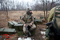"UKRAINE, 02.2016, Oblast Donetsk. Ukrainian-Russian conflict concerning Eastern Ukraine / Foreign volunteers (""Task Force Pluto"") fighting with the far-right militia Pravyi Sektor against the Russian-backed separatists: Ben (Austria) sits on empty ammunition boxes behind the frontline to talk to his comrades after returning from a position close to the enemy's. © Timo Vogt/EST&OST"