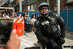 A Seattle Police officer looks on as protestors move through downtown Seattle during the Solidarity Against Hate rally Sunday August 13, 2017.