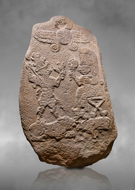 """Aslantepe Hittite relief sculpted Stele. Limestone, Aslantepe, Malatya, 1200-700 B.C. Anatolian Civilizations Museum, Ankara, Turkey.<br /> <br /> Under the winged sun disk, is a god standing on a lion and across the god is a sitting goddess. The hieroglyphs reads """"Karhuhas, the stag god"""" for the god, and """"Kubaba"""" for the Goddess. <br /> <br /> Against a grey art background."""