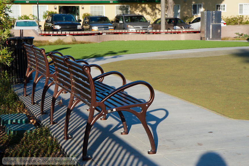 "Two benches sit on one side of Circle Park, a pocket park located on Park Circle Drive in Anaheim, California.  Artificial turf makes up the ""lawn"" in the park, with soft rubberized matting making up the surface of the play area."