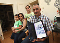REFUGEE CRISIS IN AUSTRIA. GEORGE CASE STUDY. LEFT TO RIGHT: SUBHY, 7, DIALA, LEYLA, 10 AND GEORGE HOLDING BEFORE AND AFTER PHOTOS OF HIS HOUSE IN  ALEPPO. PHOTO BY CLARE KENDALL. 12/08/15.