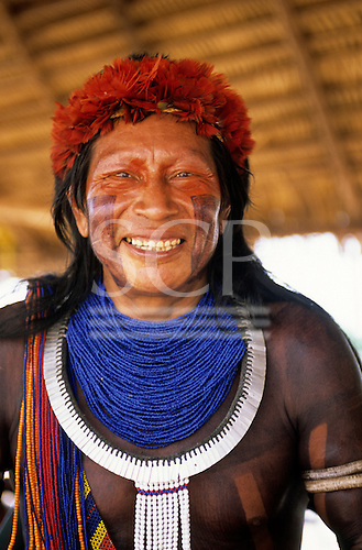 Bacaja village, Brazil. A Xicrin Indian man with bracelets, necklaces, headdress and smiling; Amazon, Para State.