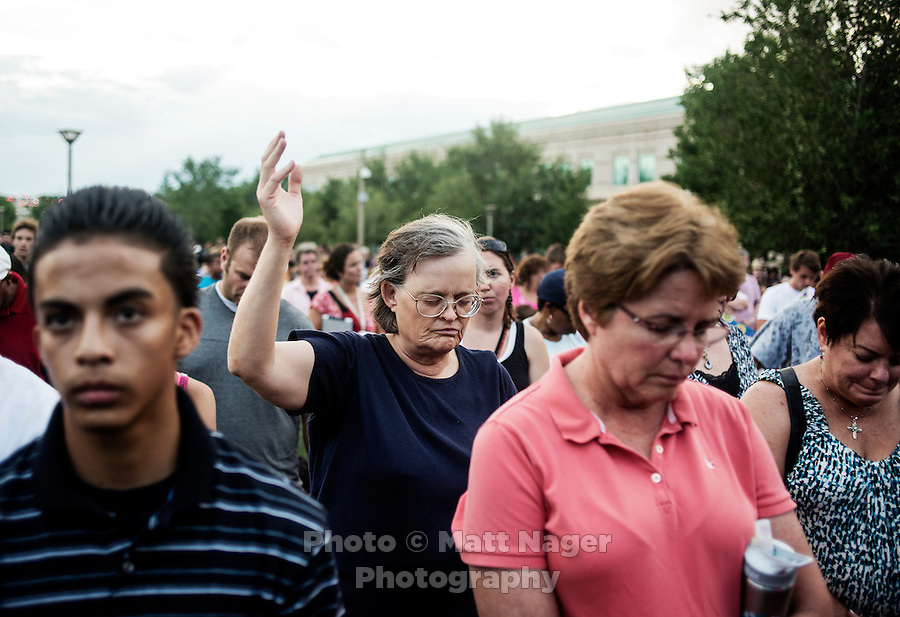People mourn for the 12 victims of the mass shooting at the Aurora Century 16 movie theater during a prayer vigil at the Aurora Municipal Center, in Aurora, Colorado, Sunday, July 22, 2012. Suspect James Holmes, allegedly went on a shooting spree and killed 12 people and injured 59 during an early morning screening of 'The Dark Knight Rises.'..Photo by MATT NAGER