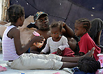 A family in a makeshift tent city in the yard of a partially destroyed school in the Pean district of Port-au-Prince, the capital of Haiti, which was ravaged by a January 12 earthquake.