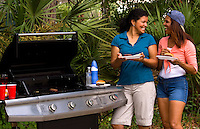 Two hispanic women enjoying picnic food outdoors at home with grill