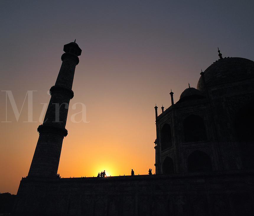 Low-angle view of the Taj Mahal outlined against a dramatic sunset sky; Agra, Indi
