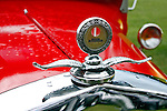 Fire-engine red, rain-spotted hood of a 1929 Ford highlights the Boyce Motormeter with its sliver wings reflected in the shiny chrome of the grill frame at the 2010 Wings 'n' Wheels Showcase, Galway, New York. Raindrops hang on the wings and are clearly seen in the reflection.