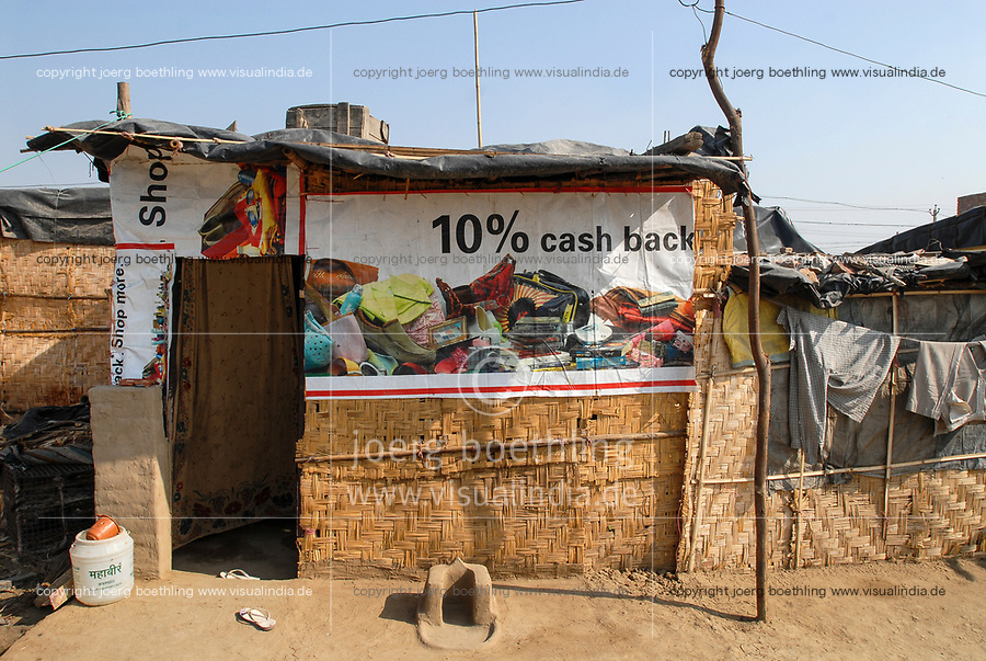 INDIA, New Delhi, forced shifted slum dweller at Slum Naglamachi at outskirts of Dehli, the people are mosty dalits, hut with old advertisement banner 10 percent cash back  / INDIEN  Neu Delhi , <br /> zwangs umgesiedelte Dalits im Slum Naglamachi am Stadtrand von Dehli