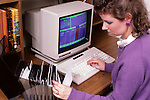 Woman working on old computer doing her household budget looking at floppy disks