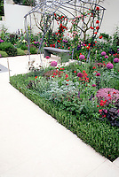 Patio with garden bench, modern upscale arbor trellis, climbing red and pink mixture of roses, purple allium ornamental onions, thymus herb thymes, rosemary border (Rosmarinus), white wall, backyard landscaping with lots of lush flowers