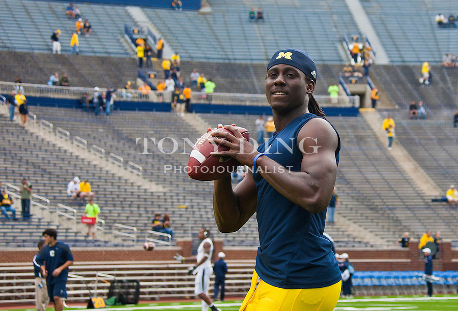 Michigan quarterback Denard Robinson throws practice passes during warmups before an NCAA college football game with Connecticut, Saturday, Sept. 4, 2010, in Ann Arbor, Mich. (AP Photo/Tony Ding)