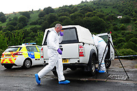 Pictured: Police forensics officers at the house where the body of David Gaut was discovered in New Tredegar, Wales, UK. Wednesday 08 August 2018<br /> Re: Three men have been arrested after a man was found dead at a house in New Tredegar, Wales, UK.<br /> David Gaut, 54, was found in Long Row, in the Elliots Town area of New Tredegar, on Saturday, August 4.<br /> Two two-storey terraced homes, owned by Caerphilly council, have been cordoned off and police officers are patrolling the area. <br /> David Gaut was jailed for life in July 1985 when he was 21 years old, for the murder and torture of17-month old Chi Ming Shek