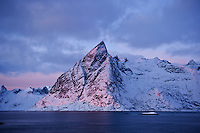 Olstinden mountain peak lit by January sun, Reine, Lofoten islands, Norway
