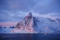 Olstinden mountain peak lit by January sun, Reine, Lofoten islands, Norway