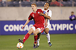 20 March 2008: Andrew Hainault (CAN) (5) plays the ball in front of Charlie Davies (USA) (right). The United States U-23 Men's National Team defeated the Canada U-23 Men's National Team 3-0 at LP Field in Nashville,TN in a semifinal game during the 2008 CONCACAF Men's Olympic Qualifying Tournament. With the victory, the United States qualified for the 2008 Beijing Olympics.