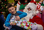 TORRINGTON, CT. 20 December 2019-122019BS09 - Skyler Morann, 7, of Winsted opens a gift given to him by Santa as he sits on Santa's lap, during a visit by Santa at the FISH of Northwestern Connecticut Homeless Shelter in Torrington on Friday. Bill Shettle Republican-American