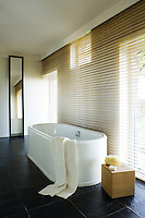 The windows of this contemporary bathroom are screened with a double-sized Venetian blind which filters the light and softens the dark slate of the floor