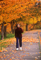 Woman walking on path in autumn.