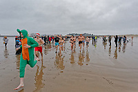 Pictured: People run to the freezing cold see. Tuesday 25 December 2018<br /> Re: Hundreds of people take part in this year's Porthcawl Christmas Swim in south Wales, UK.