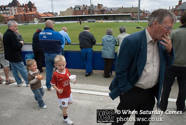 A boy in a Manchester United shirt follows an Alex Ferguson look-a-like.