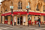 A man on a bike on Rue de Bellechass, passes Le Drop Cafe in Paris, France