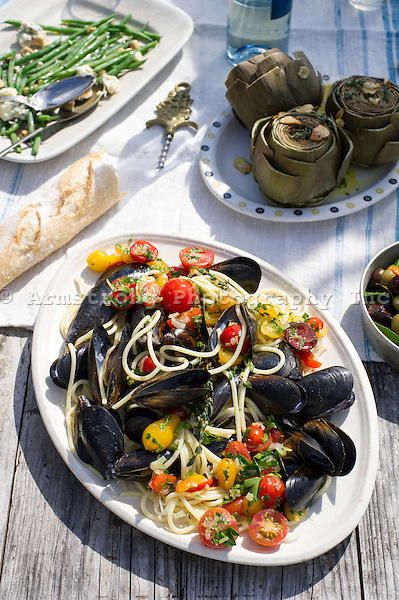 Closeup of an outdoor meal on a picnic table. In the foreground is a large plate of mussels and linguine with cherry tomatoes and parsley. Behind it is artichokes, green bean salad, baguette, olives, wine bottle, and a corkscrew.