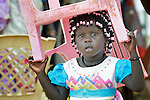 Carrying her chair, a girl leaves a Roman Catholic Mass on Easter morning, April 5, inside a United Nations base in Juba, South Sudan, where some 34,000 people have sought protection since violence broke out in December 2013. More than 112,000 people currently live on UN bases in the war-torn country, most of them afraid of tribally targeted violence. The Catholic Church has maintained a pastoral presence inside the camps.