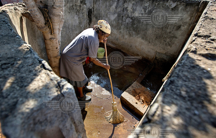 Maria Emelia Macovela (53), the cleaner at Maguiguana Primary School mops the floor of the school's dilapidated girl's toilet. She must clean the horrendous toilets used by hundreds of students on a daily basis.