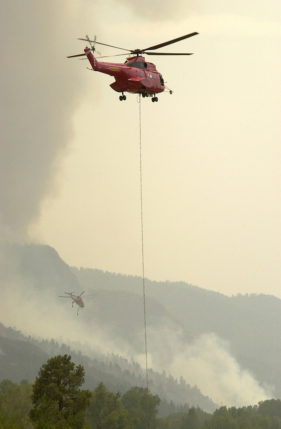 Helicopters delivering water work near the perimeter of the Missionary Ridge Fire north of Durango, Colorado in June, 2002. The fire consumed about 70,000 acres and destroyed over 50 homes.