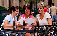 Tourist girl friends relax with drinks and look at postcards and have fun in Europe anywhere to just be friends